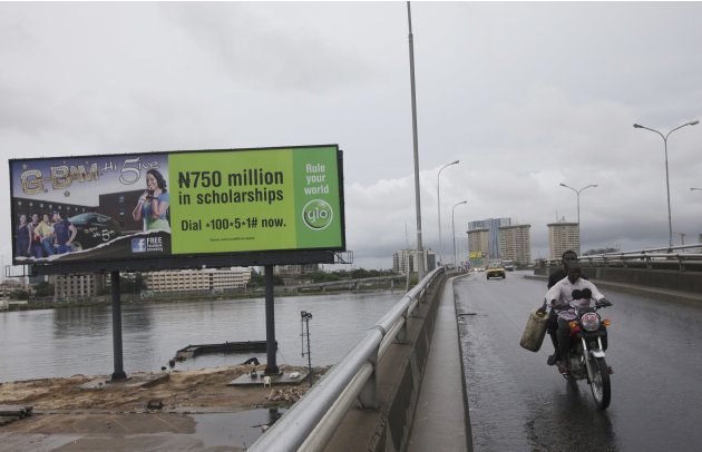 A man ride on a motor taxi past a giant advertisement bill board of Nigeria Globacom in Lagos, Nigeria, Sunday, May, 13. 2012. Nigeria has fined four mobile phone carriers a total of $7.3 million over