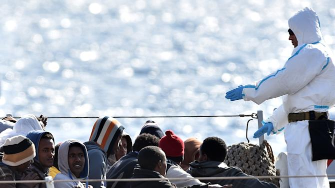 """An Italian Navy officer gives instruction to migrants who are waiting to disembark from Italian Navy ship """"Driade"""" in Messina's port, Sicily, Italy, Saturday, April 18, 2015.  Italian ships have picked up some 10,000 people, many of them refugees of war and persecution, over the past week, an unprecedented number in such a short period. The influx is putting pressure on Italy's shelter system and raising calls for a better response to the emergency. (AP Photo/Carmelo Imbesi)"""