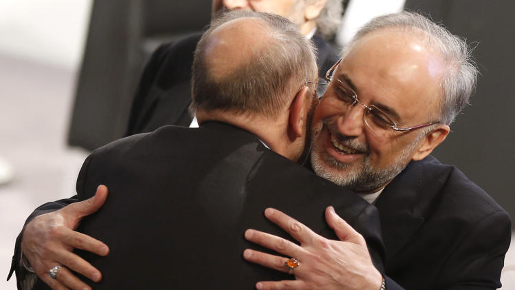 Iranian Foreign Minister Ali Akbar Salehi, right, hugs former NATO Secretary General Javier Solana as he arrives for the Security Conference in Munich, Germany, on Sunday, Feb. 3, 2013. The 49th Munich Security Conference started Friday afternoon until Sunday attended by experts from 90 delegations. (AP Photo/Matthias Schrader)