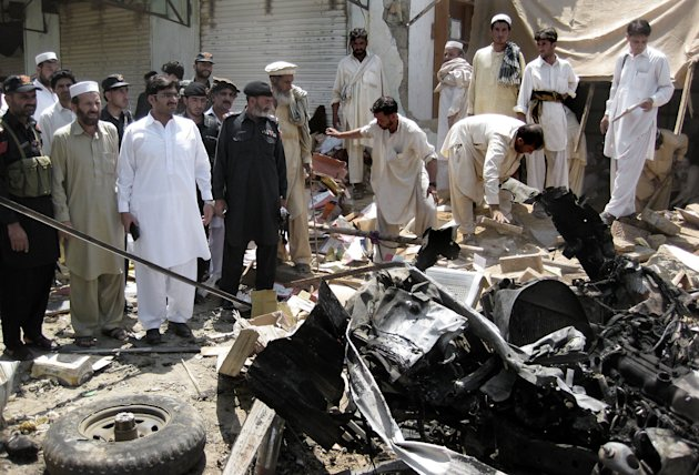 Pakistani investigators look for evidence at the site of a bomb blast in the Pakistani tribal area of Khar, Bajur, Thursday, July 26, 2012. A government official says a bomb has exploded in a market in northwestern Pakistan close to the Afghan border, killing scores of people. (AP Photo/Anwarullah Khan)