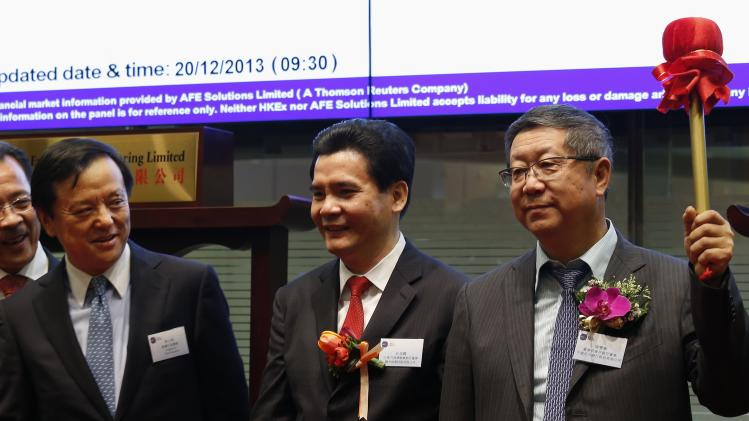 China Everbright Bank's Chairman Tang gestures after hitting gong as Hong Kong Exchange Chief Executive Li looks on during debut of the bank at the Hong Kong Stock Exchange