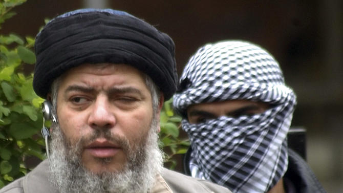 FILE - This Friday, April 30, 2004 file photo shows Muslim cleric Abu Hamza al-Masri, as he arrives with a masked bodyguard, right, to conduct Friday prayers in the street outside the closed Finsbury Park Mosque in London. Al-Masri pleaded not guilty Tuesday, Oct, 9, 2012 to charges that he conspired with Seattle men to set up a terrorist training camp in Oregon. Al-Masri entered the plea shortly before U.S. District Judge Katherine B. Forrest set an Aug. 26 trial date for al-Masri.  (AP Photo/Max Nash, File)