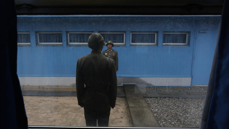In this photo taken on Monday, April 23, 2012, North Korean soldiers stand guard on the demarcation line of the Demilitarized Zone that separates the two halves of the Korean peninsula at Panmunjom, North Korea. (AP Photo/Vincent Yu)