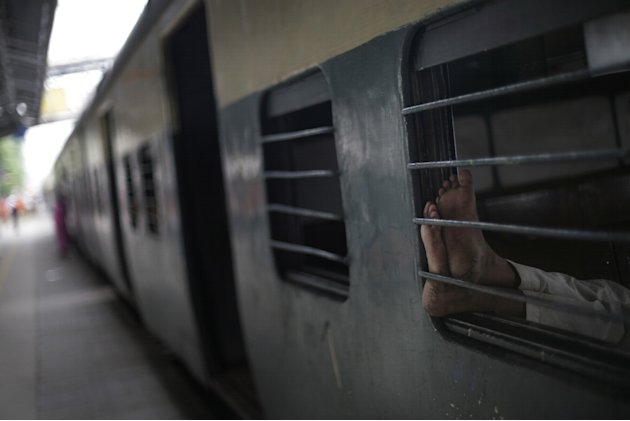 An Indian commuter sleeps inside the compartment of a stationary train following the power outage that struck in the early hours of Monday, July 30, 2012, at a train station in New Delhi, India. North