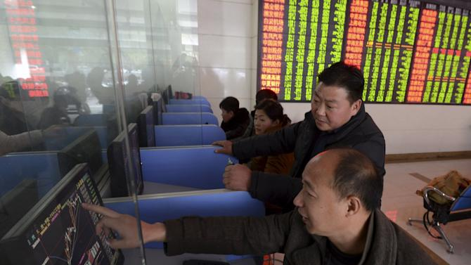 Investors talk as they look at a computer screen showing stock information at a brokerage house in Fuyang