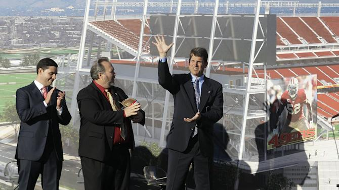 San Francisco 49ers head coach Jim Harbaugh, right, waves as he stands next to team owner Jed York, left, and Santa Clara Mayor Jamie Matthews at a groundbreaking ceremony at the construction site for the 49ers' new NFL football stadium in Santa Clara, Calif., Thursday, April 19, 2012. (AP Photo/Jeff Chiu)