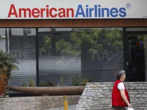 A woman walks past an American Airlines office in Caracas