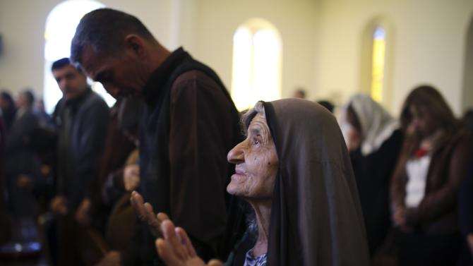 An Iraqi Christian woman prays during a mass on Christmas day at Mar Girgis Church in Baghdad