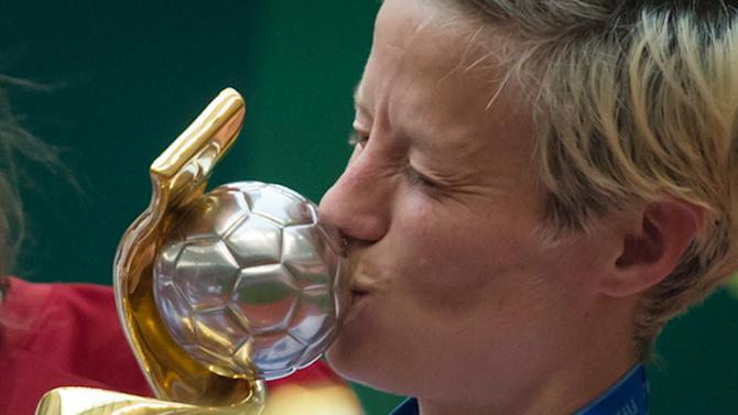 United States' Megan Rapinoe kisses the trophy after defeating Japan to win the FIFA Women's World Cup soccer championship in Vancouver, British Columbia, Canada, Sunday, July 5, 2015.   (DARRYL DYCK/The Canadian Press via AP) MANDATORY CREDIT