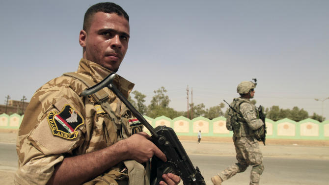 an armed Sunni militiaman wearing an Iraqi Army patch, left, and a U.S. Army soldier