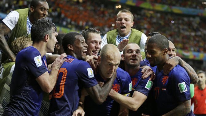 Netherlands' Arjen Robben, center, celebrates with his teammates after scoring his side's fifth goal during the second half of the group B World Cup soccer match between Spain and the Netherlands at the Arena Ponte Nova in Salvador, Brazil, Friday, June 13, 2014. (AP Photo/Natacha Pisarenko)