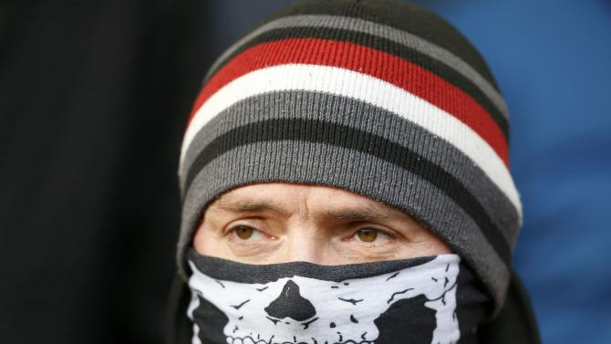 A Liverpool supporter wears a skeleton face mask before the start of their English Premier League soccer match against West Ham United at Anfield in Liverpool