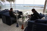 Two Russian businessmen smoke from hookahs inside a restaurant in Limassol, a coastal town in southern Cyprus February 20, 2013. REUTERS/Yorgos Karahalis