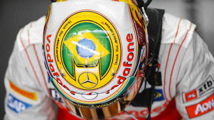 McLaren Mercedes driver Lewis Hamilton, of Britain, wearing a helmet with a painting of the Brazilian flag, gets in his car during free practice session at the Interlagos race track in Sao Paulo, Brazil,  Friday, Nov. 23, 2012. Brazil's Formula One Grand Prix will take place Sunday. (AP Photo/Victor R. Caivano)