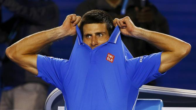 Djokovic of Serbia takes off his shirt during a break in his men's singles semi-final match against Wawrinka of Switzerland at the Australian Open 2015 tennis tournament in Melbourne