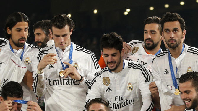 Real Madrid's Sergio Ramos, centre, who scored the team's first goal, poses alongside team mates with the trophy after winning the final soccer match between Real Madrid and San Lorenzo at the Club World Cup soccer tournament in Marrakech, Morocco, Saturday, Dec. 20, 2014. (AP Photo/Christophe Ena)