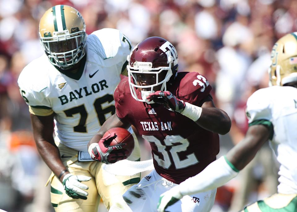 Texas A&M's Cyrus Gray (32) runs the ball against Baylor defender Nick Johnson (76) during the first half of an NCAA college football game Saturday, Oct. 15, 2011, in College Station, Texas. (AP Photo/Jon Eilts)
