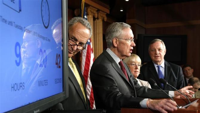 Schumer, Reid, Murray and Durbin stand with a clock counting down to a government shutdown at a news conference at the U.S. Capitol in Washington