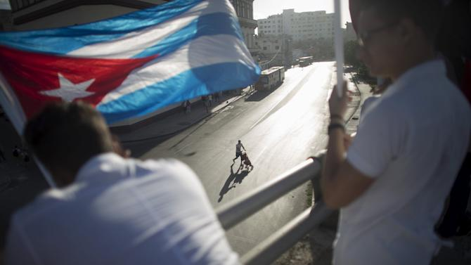 A student holds a Cuban flag as a man passes near by with a baby stroller during a ceremony in Havana November 27, 2015, marking the anniversary of the deaths of student leaders killed during the fight against Spanish colonial rule.