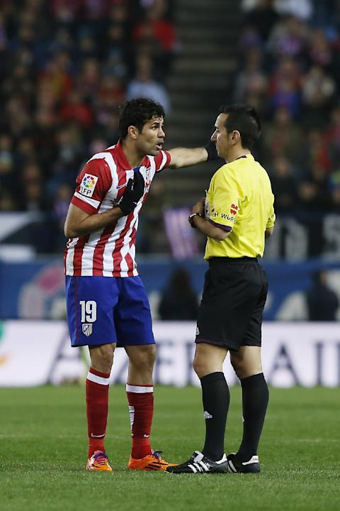 Atletico's Diego Costa, left, complains to a referee during a Spanish La Liga soccer match between Atletico Madrid and Espanyol at the Vicente Calderon stadium in Madrid, Spain, Saturday, March 15