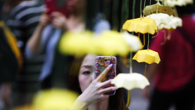A woman takes pictures of miniature paper umbrellas, the symbol of pro-democracy protesters, at their barricade in Mongkok