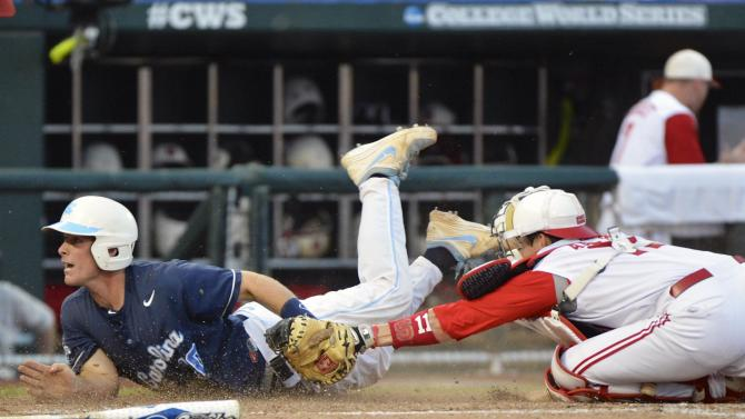 North Carolina's Brian Holberton, left, scores at home plate against North Carolina State catcher Brett Austin on a sacrifice fly by Michael Russell in the fourth inning of an NCAA College World Series elimination baseball game in Omaha, Neb., Thursday, June 20, 2013. (AP Photo/Ted Kirk)