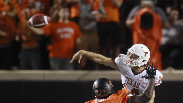 Texas quarterback David Ash (14) throws under pressure from Oklahoma State defensive tackle Calvin Barnett (99) during the third quarter of an NCAA college football game in Stillwater, Okla., Saturday, Sept. 29, 2012. Texas won 41-36. (AP Photo/Sue Ogrocki)