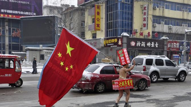 A topless man carrying a Chinese national flag and wearing cardboards printed with advertisements waves as he promotes along a street covered by thin snow in Zhumadian