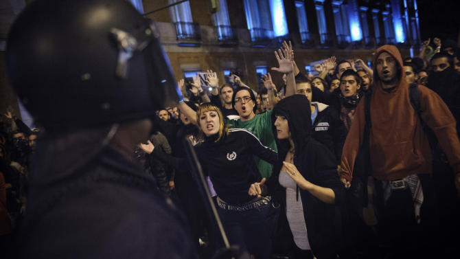 Demonstrators shout to a Spanish riot policeman after a march to the Spanish Parliament against the austerity measures announced by the Spanish government in Madrid, Spain, Tuesday, Sept. 25, 2012. Spain's government was hit hard by the country's financial crisis on multiple fronts Tuesday as protestors enraged with austerity cutbacks and tax hikes clashed with police near Parliament, a separatist-minded region set elections seen as an independence referendum and the nation's high borrowing costs rose again. (AP Photo/Daniel Ochoa De Olza)
