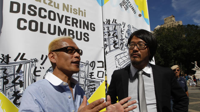 """Japanese artist Tatzu Nishi, left, speaks to reporters with the help of translator Kasuke Fujitaka during a media preview of """"Discovering Columbus,""""  Wednesday, Sept. 19, 2012 in New York.  The 810-square-foot livingroom offers spectacular views of mid-Manhattan. A 13-foot statue of Christopher Columbus stands amid the couches, lamps and coffee table. (AP Photo/Mary Altaffer)"""