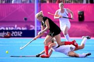 Kristina Hillmann (foreground) Of Germany challenges Charlotte Harrison (back) of New Zealnad in the women's hockey tournament at the Riverbank Stadium. New Zealand's women's hockey team held Germany to a 0-0 draw Monday to knock out the former champions and reach their first Olympic semi-final after 32 years of trying