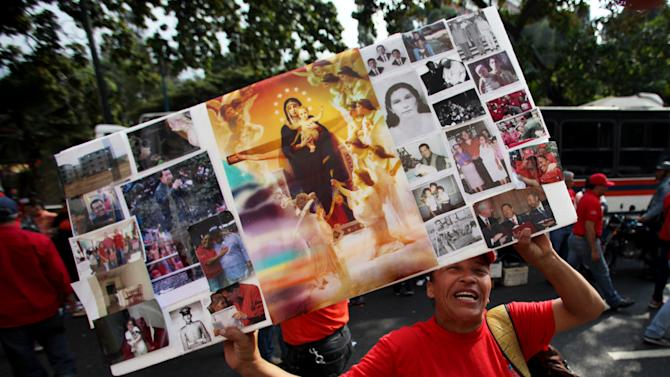 A supporter of Venezuela's President  Hugo Chavez holds up a collage of images showing Chavez and a central image of the Virgin Mary holding baby Jesus at a rally in Caracas, Venezuela, Wednesday, Jan. 23, 2013. The cult of personality that Chavez long nurtured has been flourishing like never before as he confronts an increasingly difficult struggle against the mysterious cancer that afflicts him. The connections between Chavez and Jesus are surfacing more often, having begun with Chavez himself praying to God on television, and repeatedly kissing a crucifix. (AP Photo/Fernando Llano)