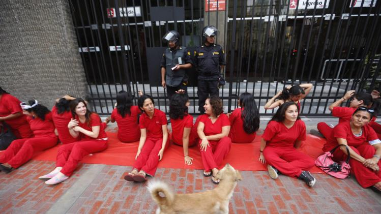 Activists dressed in red protest in front of the Ministry of Women during International Women's Day in Lima