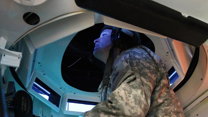 Sgt. 1st Class Donald Jones looks at the computer screens that serve as windows inside a tank simulator prior to a training exercise in Ft. Bliss, Texas, Tuesday, Jan. 22, 2013. The army is rolling out a new training platform that allows the integration of live units, simulators and computer generated forces. It is expected to allow cheaper, more frequent training. (AP Photo/Juan Carlos Llorca)