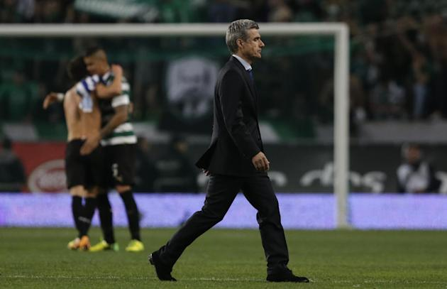 FC Porto's coach Luis Castro leaves the pitch as Sporting players hug in the background at the end of their Portuguese league soccer match Sunday, March 16 2014, at Sporting's Alvalade stadium