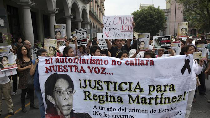"""Journalists march together during a protest to demand justice in the Regina Martinez case, a journalist killed a year ago and an end to more recent attacks on the press in Veracruz, Mexico, Sunday April 28, 2013. Journalists in several states organized a demonstration on Sunday to mark the first anniversary of the murder of Regina Martinez, a correspondent of the magazine Proceso. Attacks have become so common that many Mexican news media have announced they will no longer cover stories related to drug cartels.The issue has become so serious that Mexico's congress passed a bill this month that would allow journalists to request that federal prosecutors and federal judges investigate attacks on them, and would make federal intervention mandatory in some cases. It has been sent to the president for his signature. Banner says: """"Authoritarian rule will not shut up our voice... JUSTICE for Regina Martinez! One year after the state crime: We do not believe you!""""AP Photo/Felix Marquez)"""