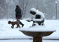 A man walks his dog past the snow covered &quot;Boy and Bird&quot; fountain in the Boston Public Garden in Boston, Friday, Feb. 8, 2013. Mass. Gov. Deval Patrick declared a state of emergency Friday and banned travel on roads as of 4 p.m. as a blizzard that could bring nearly 3 feet of snow to the region began to intensify. As the storm gains strength, it will bring &quot;extremely dangerous conditions&quot; with bands of snow dropping up to 2 to 3 inches per hour at the height of the blizzard, Patrick said. (AP Photo/Charles Krupa)