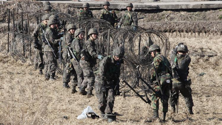 South korean Army soldiers set up barbed wire fence during an exercise against possible attacks by North Korea near the border village of Panmunjom in Paju, South Korea, Monday, March 11, 2013. South Korea and the U.S. on Monday kicked off an annual military drill amid worries about a possible bloodshed following North Korea's threat to scrap a decades-old war armistice and launch a nuclear attack on the U.S. (AP Photo/Ahn Young-joon)