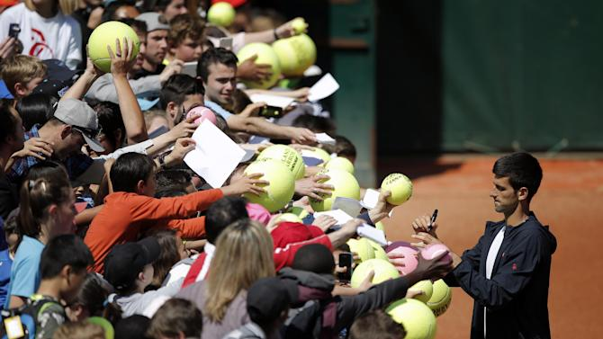 Serbia's Novak Djokovic signs autographs after a training session for the French Tennis Open at the Roland Garros stadium, in Paris, Saturday, May 23, 2015. The French Open starts Sunday. (AP Photo/Francois Mori)
