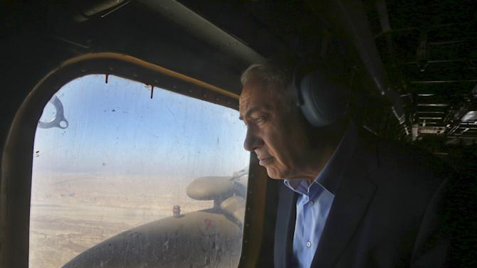 Israeli Prime Minister Benjamin Netanyahu looks out of a military airplane's window as he makes his way to visit the border fence between Israel and Jordan