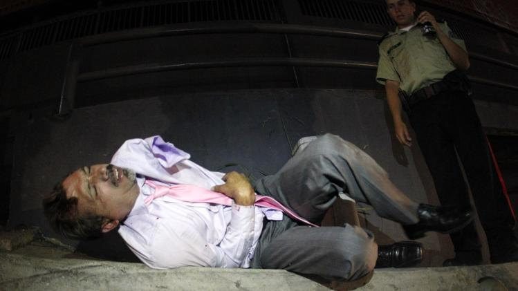 A policeman stands next to an injured driver as he lies on the ground after being beaten up by protesters in Caracas