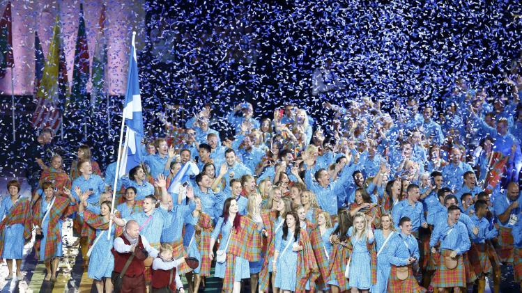 The flag of Scotland is carried by Euan Burton as they arrive during the opening ceremony for the 2014 Commonwealth Games at Celtic Park in Glasgow, Scotland