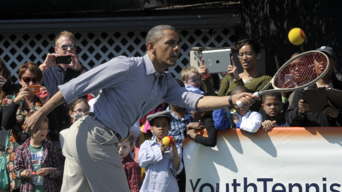 President Barack Obama eyes the ball during a tennis game at the annual Easter Egg Roll on the South Lawn of the White House in Washington, Monday, April 1, 2013. (AP Photo/Susan Walsh)