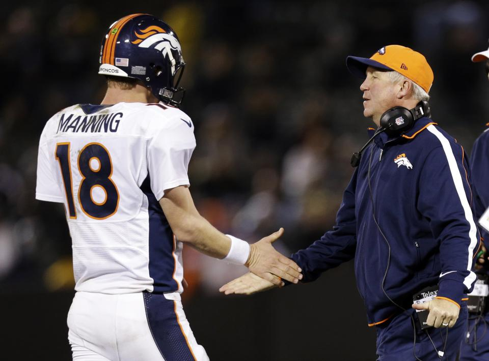 Denver Broncos quarterback Peyton Manning, left, is greeted by head coach John Fox at the end of an NFL football game against the Oakland Raiders in Oakland, Thursday, Dec. 6, 2012. Denver won 23-13. (AP Photo/Marcio Jose Sanchez)