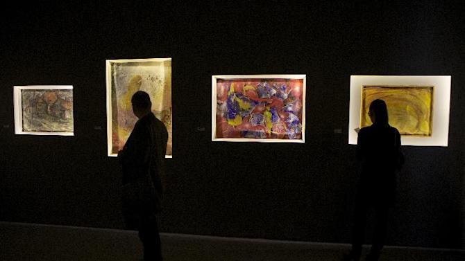 In this photo taken on Thursday, Dec. 5, 2012, visitors look at canvases banned in 1962 by Soviet leader Nikita Khruschev and now exhibited at Moscow's Manezh hall, Russia. Fifty years later, some of the banned canvases are on display again at the same Manezh hall, at a time when critics compare Khruschev's ban to recent charges against the Pussy Riot band and artists whose paintings have angered the Kremlin and Russia's dominant Orthodox Church. (AP Photo/Alexander Zemlianichenko)