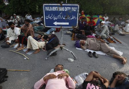 Supporters of Mohammad Tahir ul-Qadri, Sufi cleric and leader of political party Pakistan Awami Tehreek (PAT), sleep at the entrance of the parliament house in Islamabad