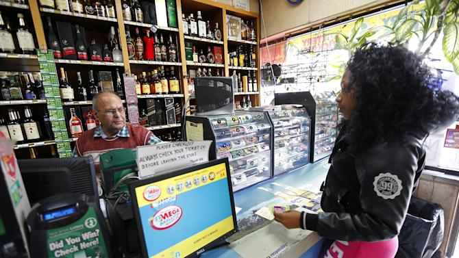 Pravin Mankodia, sells a lottery ticket to Nature Haley at Eagles Liquors in Passaic, N.J. Monday, March 25, 2013. Mankodia sold the winning $338 million Powerball ticket that was claimed by an unidentified New Jersey Resident. (AP Photo/Rich Schultz)