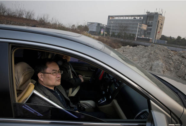 In this Monday, Jan. 20, 2014 photo, Zhou Wangyan, head of the Liling city land resources bureau, sits in a car in Zhuzhou city in central China's Hunan province across the road from Qiaotoubao, a