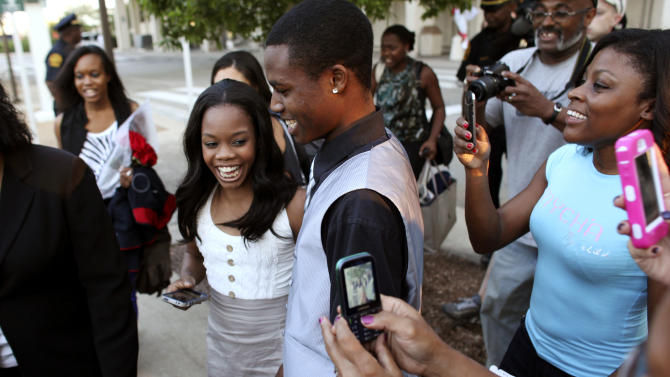 Gabby Douglas, left, 2012 London Summer Olympics gold medal-winning gymnast, laughs with her brother, John Douglas, after arriving at Norfolk International Airport, Thursday, Aug. 16, 2012, in Norfolk, Va., on her way to visit her hometown of Virginia Beach, Va. (AP Photo/Virginian-Pilot, Ross Taylor)  MAGS OUT