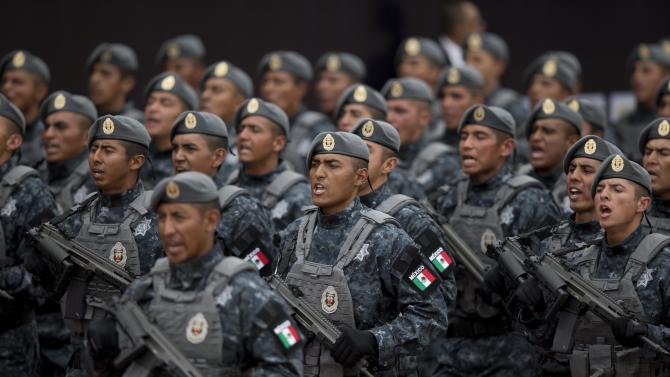 Officers belonging to Mexico's newest police force, known as the gendarmerie, march during the launching ceremony for the new force at the Federal Police headquarters in Mexico City, Friday, Aug. 22, 2014. Gendarmerie members will be a division of the federal police and will be sent to protect areas like those where wheat and sorghum farmers, banana growers and mining firms have been hit by organized crime. (AP Photo/Eduardo Verdugo)